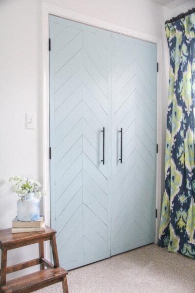 sliding closet doors updated to hinged doors with a modern blue herringbone wood plank design.