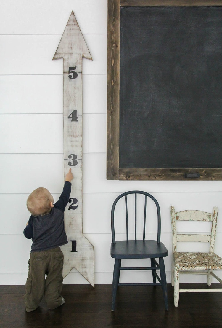 toddler standing next to diy wood growth chart.