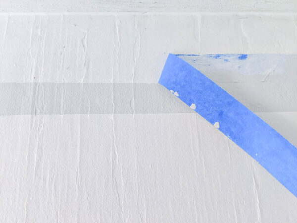 pulling painter's tape off after painting stripes on a rough plywood floor.