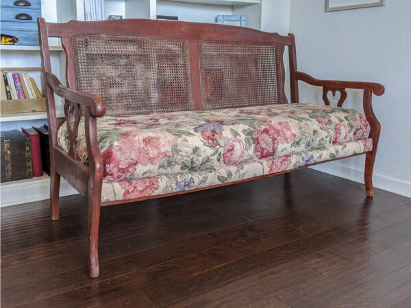 wooden settee with a cane back, a poofy floral seat, and heart cutouts on the arms.