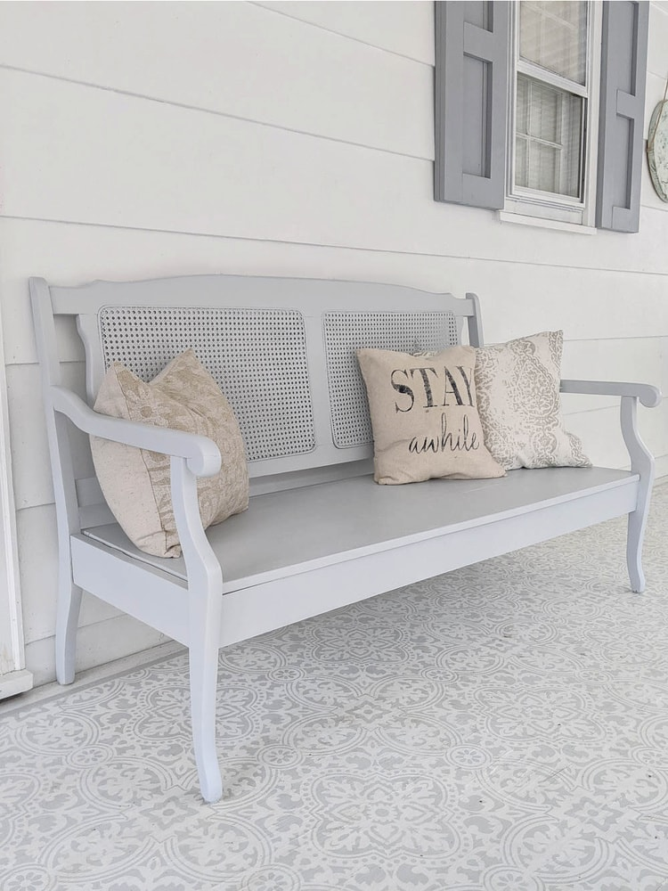 Completed bench with wooden seat and light gray exterior paint on porch.