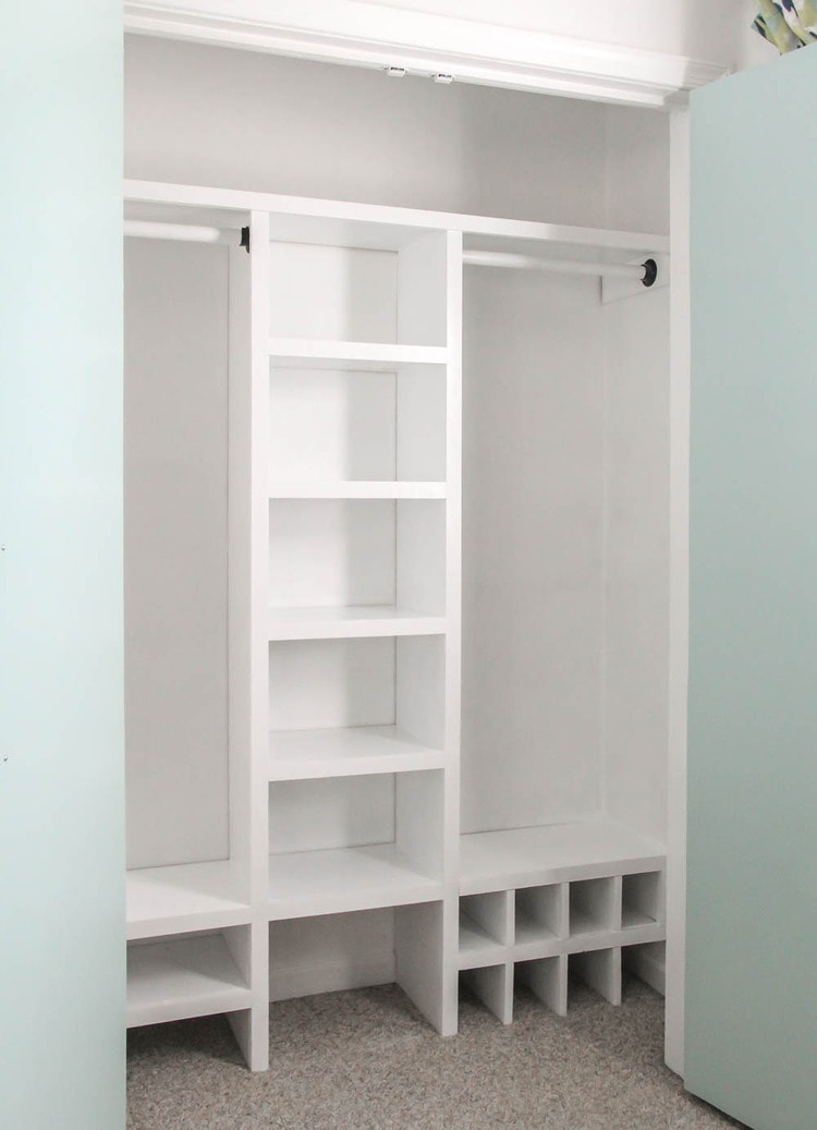 Finished DIY closet organizer with middle shelves, two hanging rods, and lots of shoe shelves.