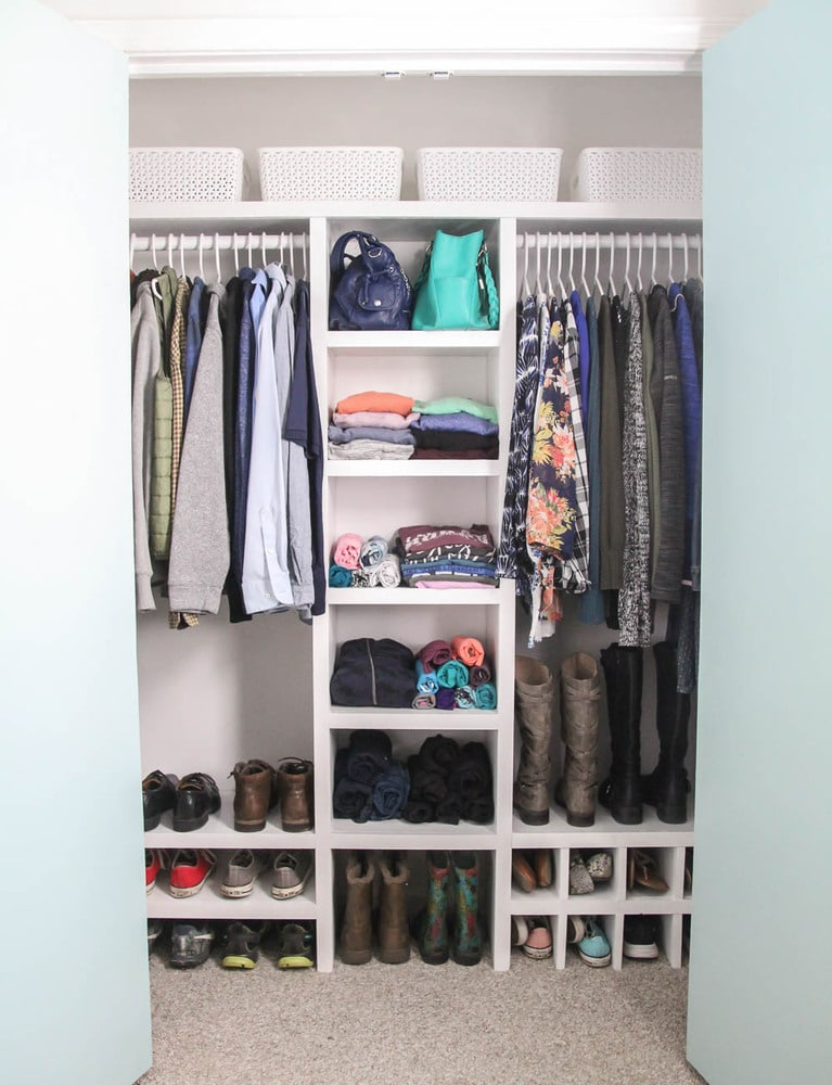 Finished DIY closet organizer filled with clothes, shoes, and accessories.