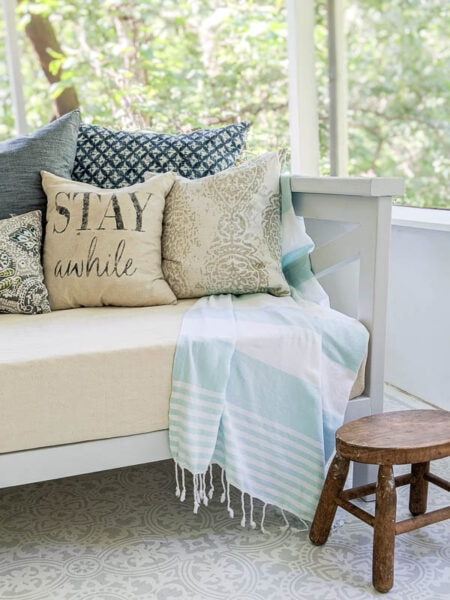 wooden daybed on porch with cover and pillows protected with waterproofing spray.