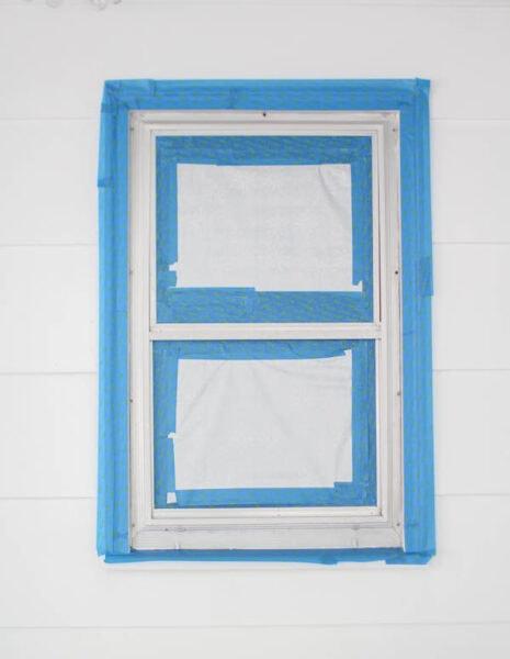 taping around aluminum windows to prepare them to be spray painted.