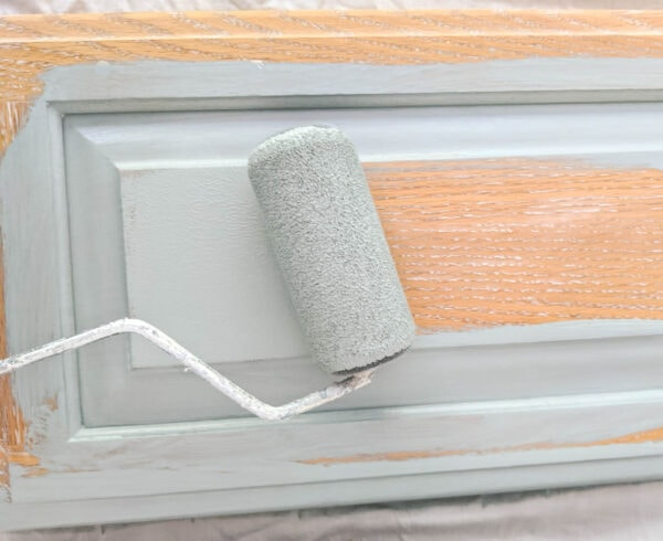 painting a cabinet door with a flocked paint roller and blue paint.