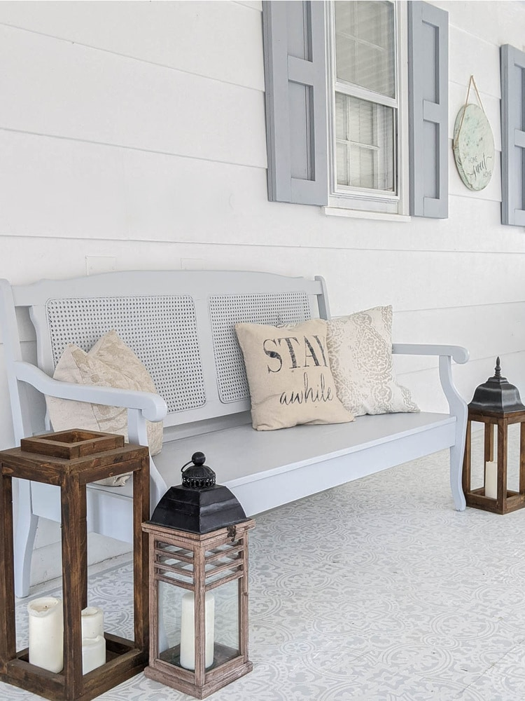 painted bench on porch with pillows and candle lanterns around it.