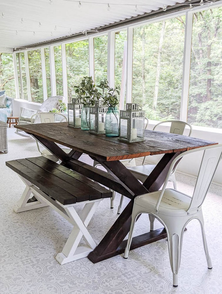 finished bench with DIY farmhouse table and metal chairs on screened-in porch.