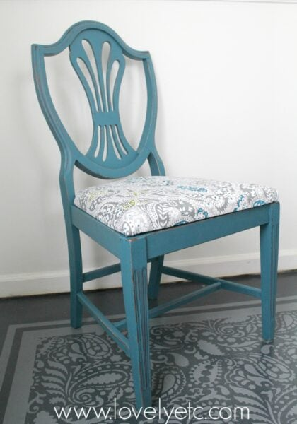 Wooden dining chair painted blue and reupholstered using fabric from a shower curtain.