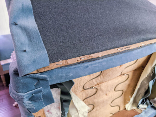 Attaching the chair back with a cardboard strip and tack strips.