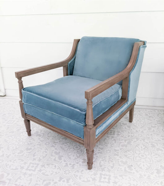 Chair reupholstered with blue velvet fabric with a painted wood frame.