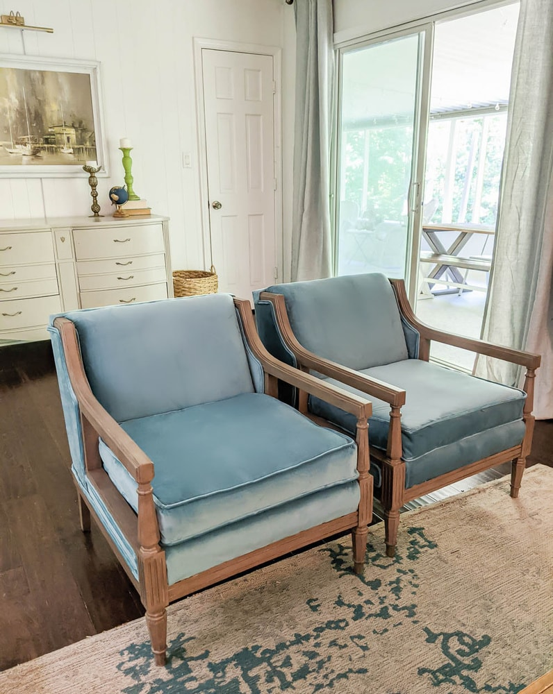 Pair of vintage chairs reupholstered with blue velvet fabric in living room.