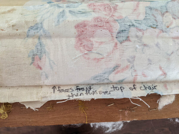 Piece of old upholstery fabric labeled with a marker to show where on the chair it goes.