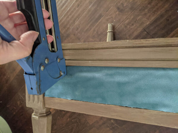 Stapling fabric along the arms of the chair using a staple gun.