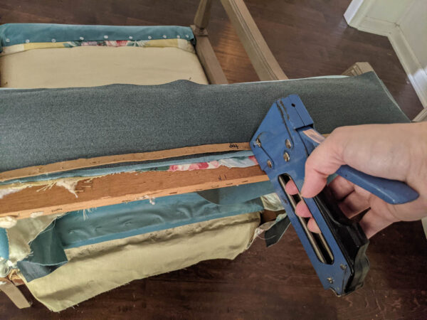 Stapling a cardboard strip onto the chair for a clean upholstery line.