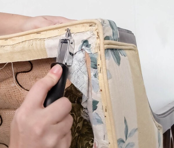 Using an upholstery staple remover to remove old staples and upholstery from the chairs.
