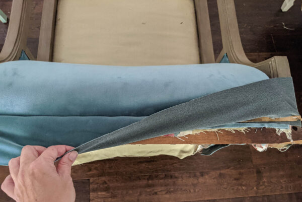 Folding the newly attached fabric over the cardboard strip to show the clean line where it attaches.