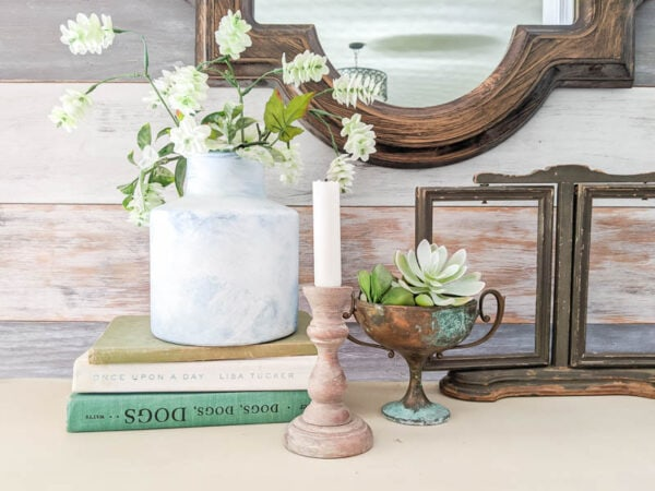 Candlestick painted with a weathered wood paint finish on a table next to old books and plants.