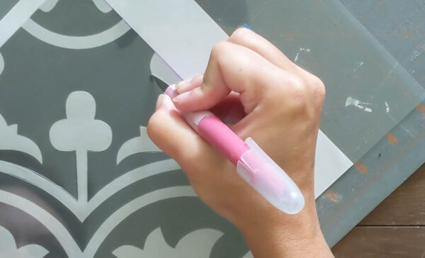 Using a craft knife to cut a stencil design from plastic.