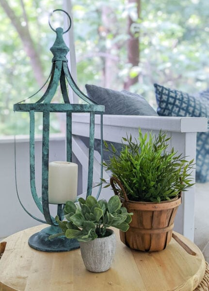 Thrifted candle lantern after it has been painted with a patina finish on a small table next to two plants.