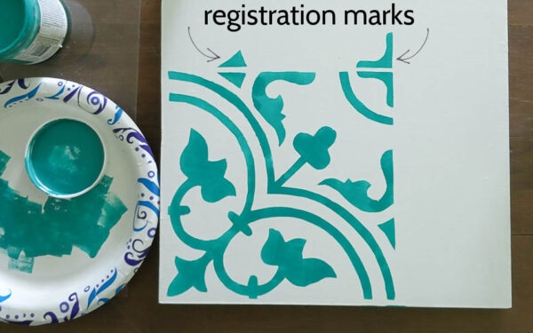 White board stenciled with DIY stencil showing the extra bits of the pattern that serve as the stencil registration marks.