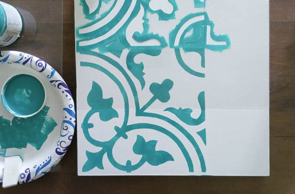 Stenciling a sample board with my DIY tile stencil and lining up the repeating design using the registration marks.