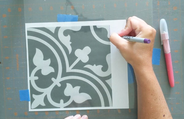 Using a super fine tip Sharpie to trace a patterned tile design onto a stencil blank.