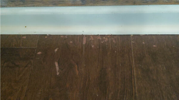 Using wax fill stick to fill scratches on wood floor.