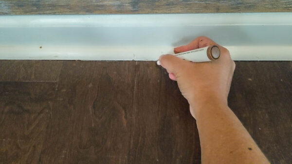 Using wood repair markers to fix scratched wood floor.