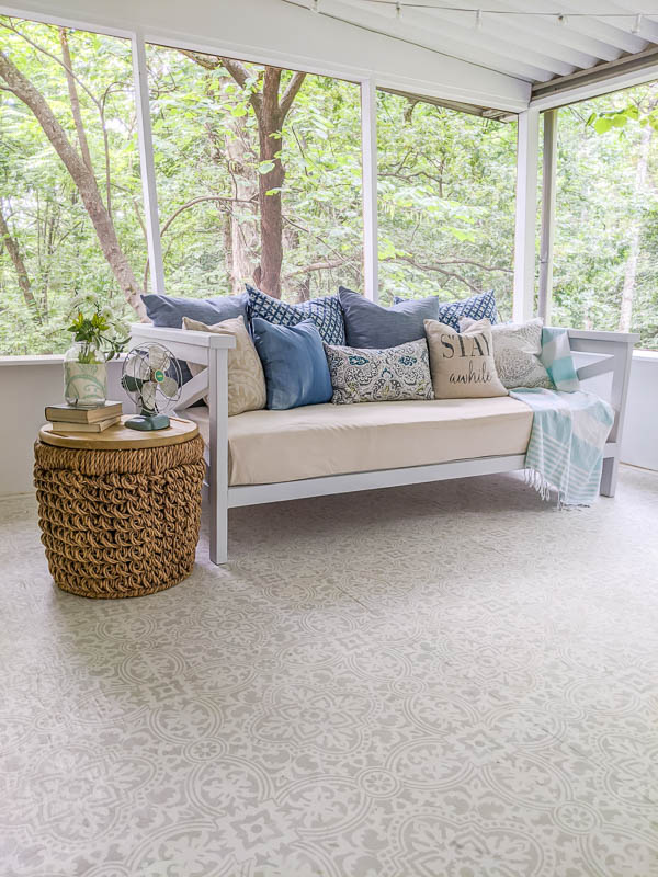 DIY daybed with piles of pillows and a basket table on a screened-in porch.