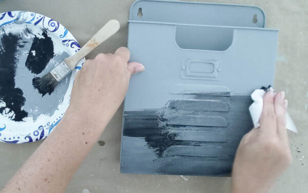 Rubbing a black color wash onto a wall pocket painted gray.