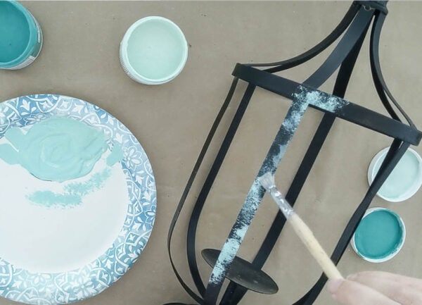 dry brushing blue-green paint onto a metal outdoor lantern for a faux patina finish.
