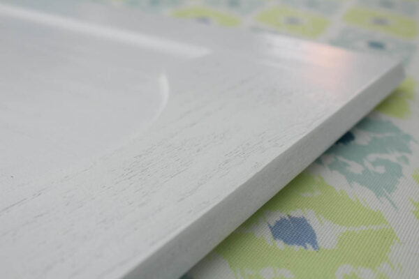 cabinet door painted white with pronounced wood grain showing through.