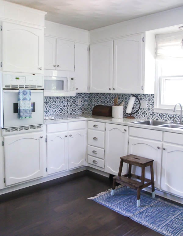 Kitchen with oak cabinets painted white, painted countertops, and stenciled backsplash.