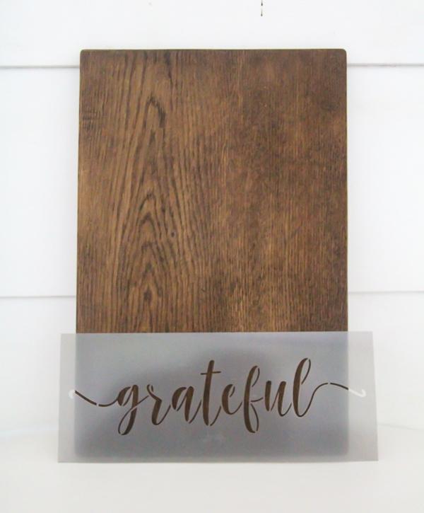 plain wood cutting board next to stencil that says grateful.