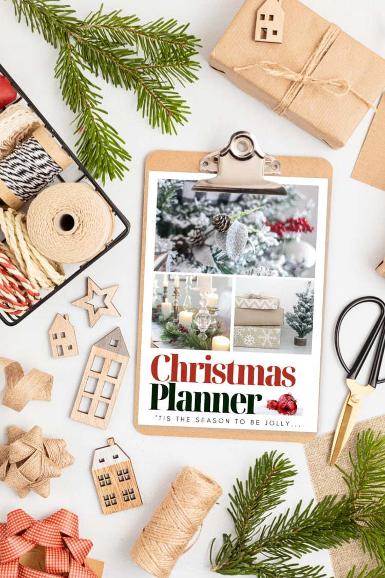 cover of free Christmas planner on clipboard surrounded by Christmas decor.