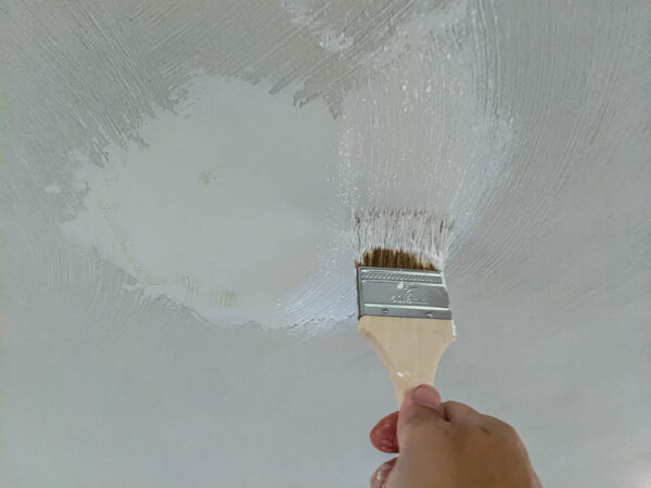 using a chip brush to add texture to a smooth patch on the ceiling.