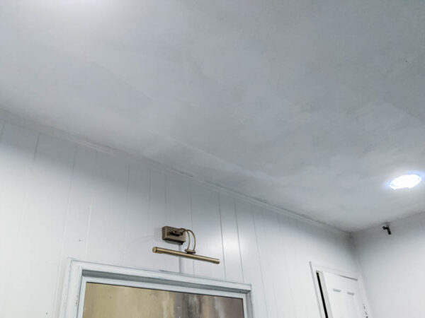 Ceiling after first coat of white paint with uneven finish.