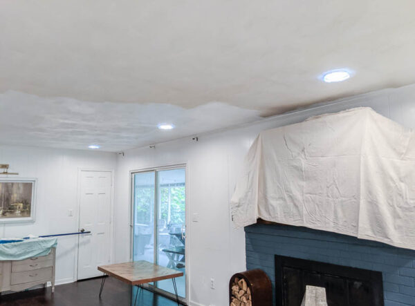 ceiling half painted with fresh white paint and half unpainted.